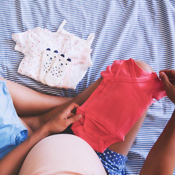 Schwangere Frau mit Erstausstattung fürs Baby