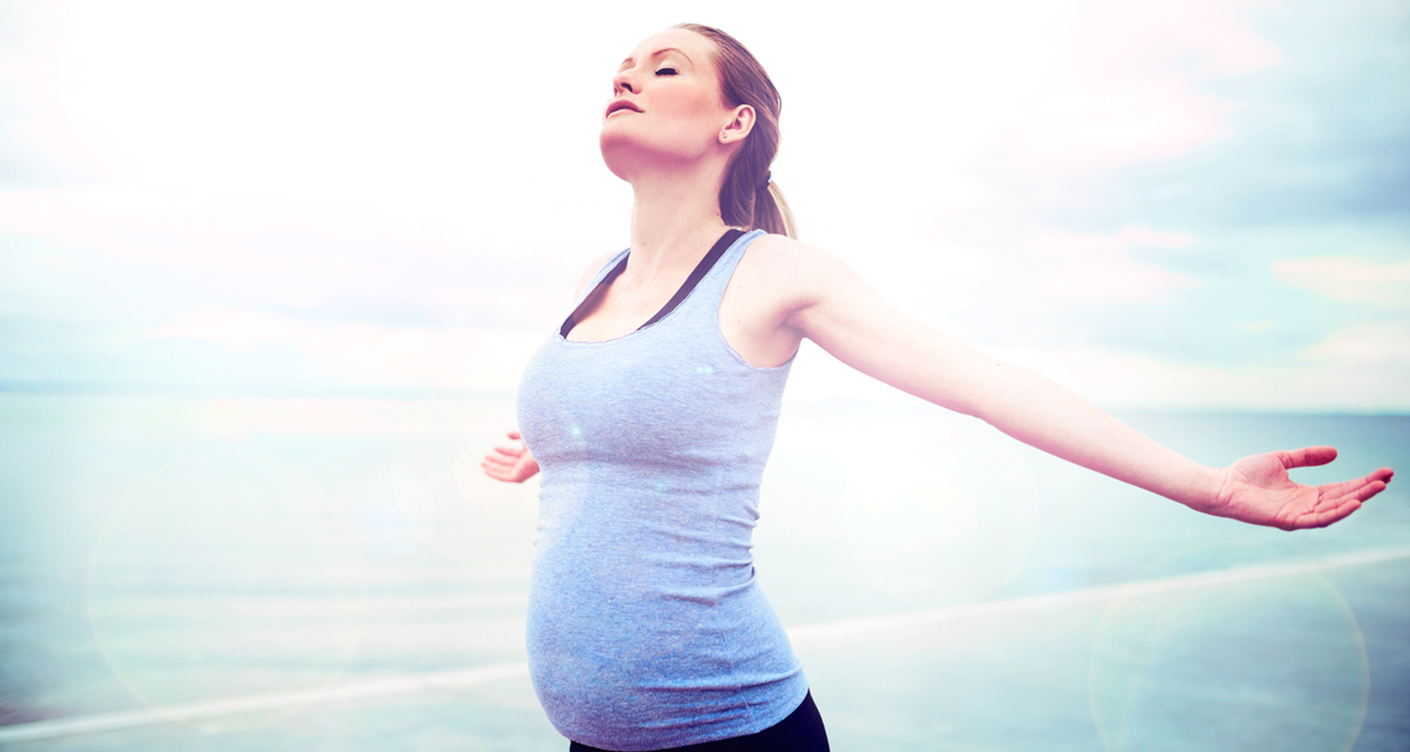 Pregnant woman embracing the sunshine standing overlooking the ocean with her arms outstretched and head raised to the sun with closed eyes
