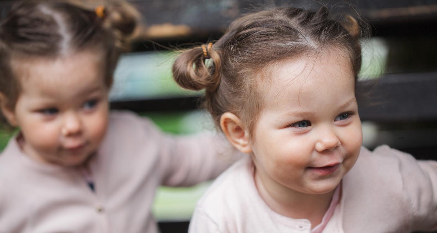 Eineiige Zwillinge Mädchen lächelnd