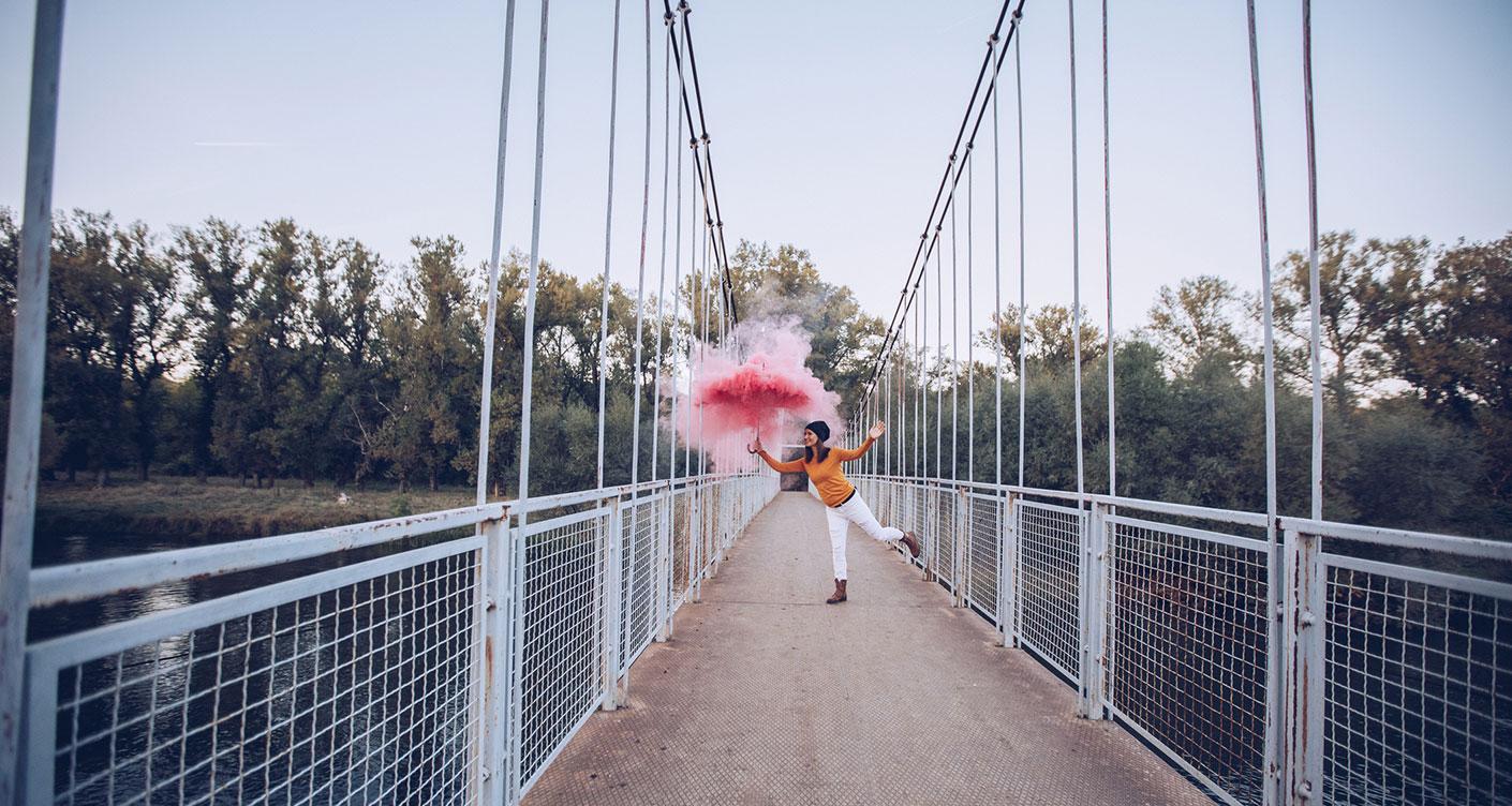 Frau mit Schirm auf Brücke