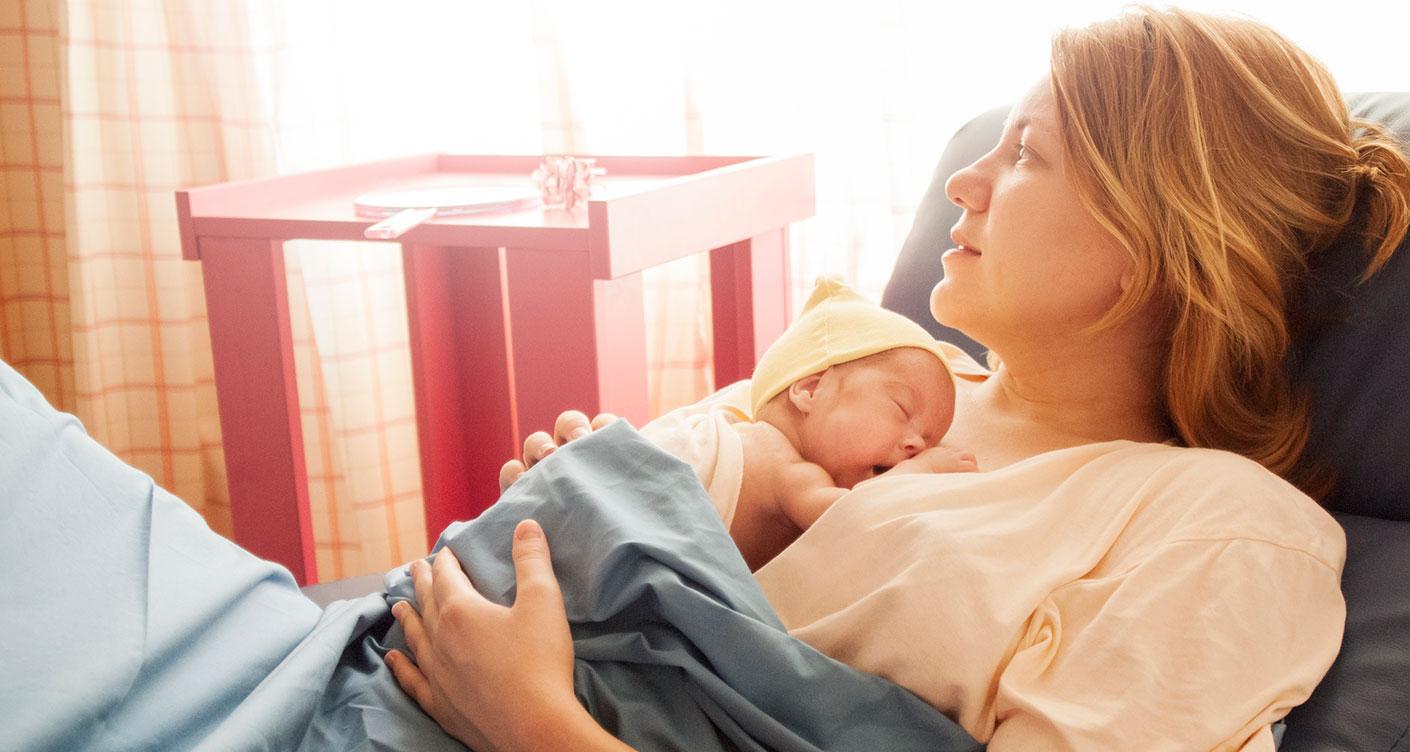 Frau mit Baby im Krankenhaus nach Kaiserschnitt