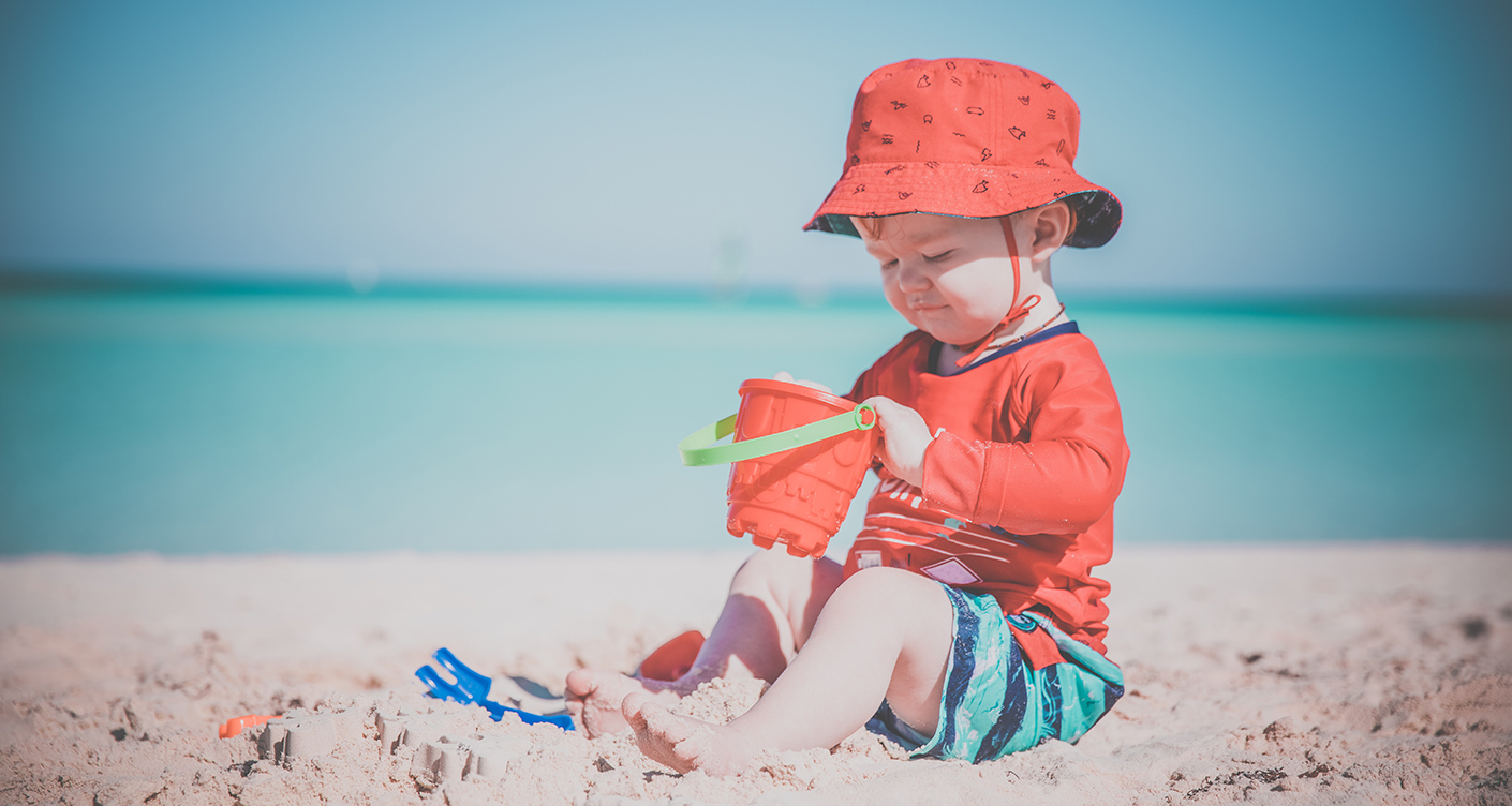 Baby spielt am Strand