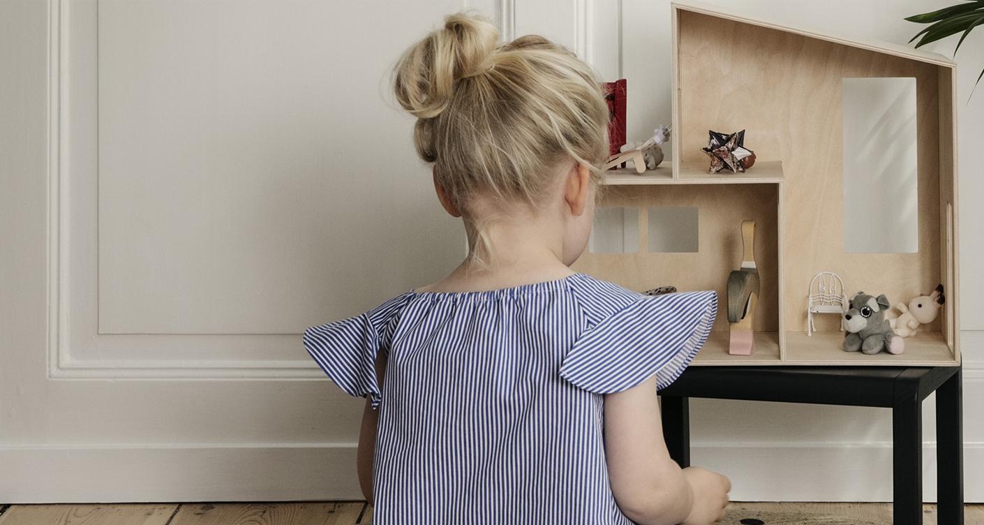Maedchen spielt mit Puppenhaus aus Holz Kinderzimmer Zuhause Spielzeug